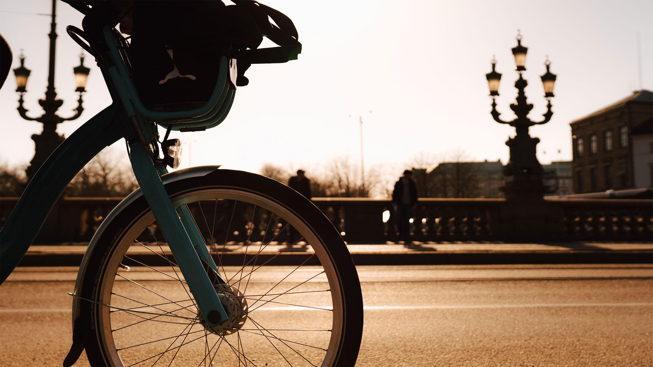 Cykelhjul i stadsmiljö i motljus